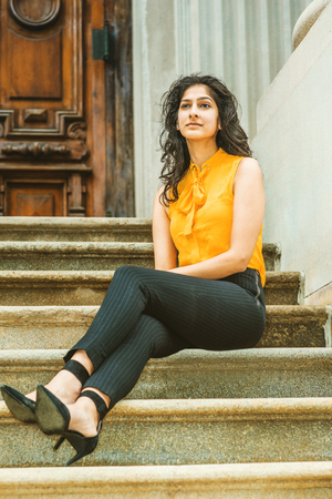 East Indian American College Student in New York. Wearing sleeveless orange shirt, striped pants, high heels, business woman sitting on stairs outside office building, taking break.