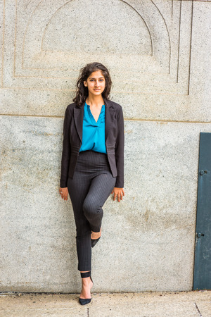 Modern East Indian American Student. Dressing in black blazer, blue under shirt, striped pants, heels,  a young girl with long curly hair standing against wall on campus, smiling, looking at you.