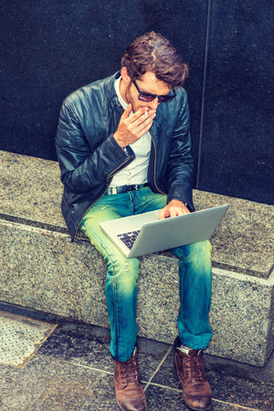Wearing black leather jacket, jeans, boot shoes, sunglasses, a young guy with beard sitting on marble bench, smoking cigarette, working on laptop computer, trying hard to solve problems after working. Stock Photo