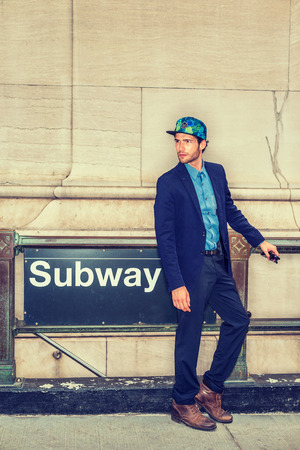 Wearing fashionable hat with sign NYC - New York City, blue suit, brown boot shoes, a young guy with beard standing by subway station, looking around, waiting for you. Filtered effect