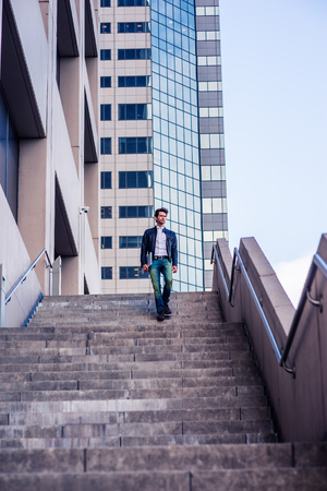 Young man with beard, wearing leather jacket, jeans, arm carrying laptop computer, walking down stairs outside office high building after busy working day, going home. Filtered look with purple tint.