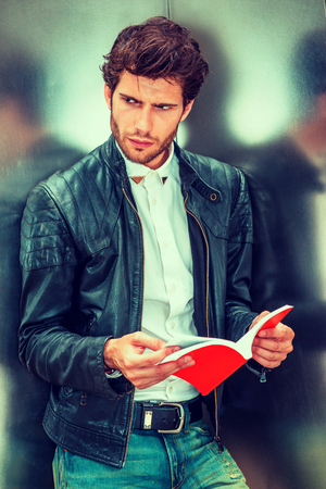 Critical reading, thinking, plan in business. Guy with beard, wearing black leather jacket, white shirt, leaning on silver metal wall, reading red book, turning around, thinking, during working break. Archivio Fotografico