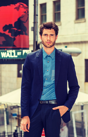 Serious businessman working in New York. Wearing blue suit, shirt, a young handsome guy with beard standing on Wall Street, frowned, sad, expressed frustrating, troubling feelings. Filtered effect.