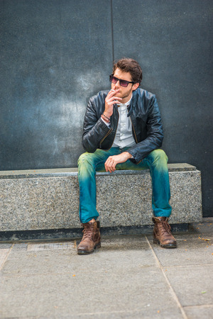 Wearing black leather jacket, blue jeans, brown boot shoes, sunglasses, a young guy with beard sitting on marble bench in corner, smoking cigarette during working break, trying mind calming down Imagens