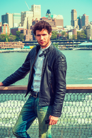European man traveling on East River in New York. Wearing black leather jacket, jeans, a guy with beard, standing at harbor, looking around. Crowed buildings on background. Filtered effect.