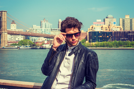 European businessman traveling in New York. Wearing leather jacket, holding sunglasses, a guy with beard, standing by river, looking down, sad, think. Brooklyn bridge, high buildings on background.