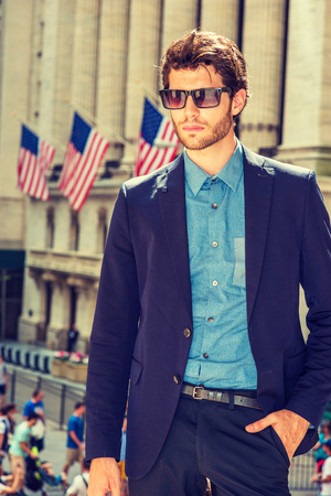 Serious European businessman in New York. Dressing in blue suit, shirt, wearing sunglasses, a young handsome guy with beard standing in business district, looking down, thinking. Filtered effect.