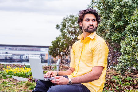 Raining - grainy, drizzling, wet feel. Young East Indian American Man with beard, wearing short sleeve yellow shirt, sitting outside in New York, working on laptop computer, looking away, thinking.
