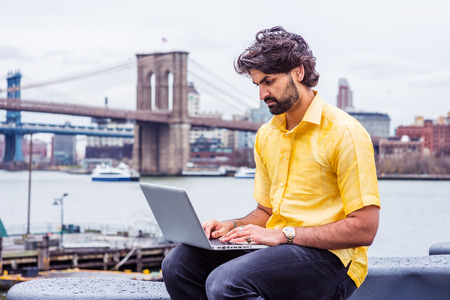 Raining - grainy, drizzling, wet feel. Young Man with beard traveling in New York, wearing short sleeve yellow shirt, sitting by East River, working on laptop computer. Bridges, boat on background. Banco de Imagens - 121421747
