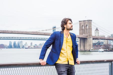 Deszczowy dzień - ziarnisty, mokry odbiór. Młody Indianin z brodą, podróżujący po Nowym Jorku, stojący nad East River, rozglądający się i czekający na Ciebie. Manhattan, mosty Brooklyn w tle