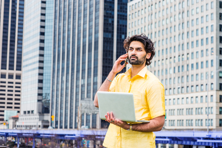 Raining day- grainy, wet feel. Young East Indian American Man with beard traveling in New York City, wearing yellow suit, standing in front of high buildings, holding laptop computer, talking on phone