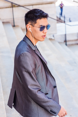 Young Asian American Businessman working in New York, dressing in gray fashionable blazer, wearing white earphone, blue sunglasses, listening music, walking down stairs from office building.