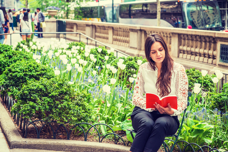 I love reading. Young Eastern European Woman with long hair, wearing white, lace cut out long sleeve shirt, sitting by flowers at street park in Middletown of Manhattan, New York, reading red book.