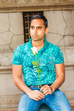 Young Hispanic American Man missing you, waiting for you, wearing green patterned Polo shirt, holding white rose, sitting on old street in New York, looking away, thinking. Reklamní fotografie