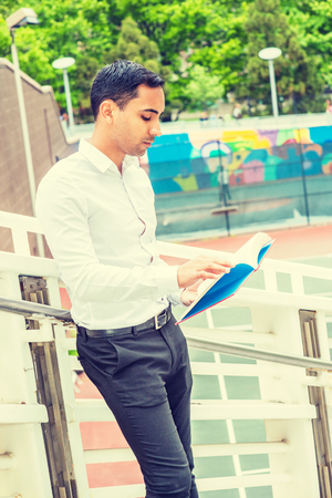 Young Hispanic American Man studying in New York, wearing white shirt, black pants, holding red book, standing against railing by tennis court on campus, looking down, reading, thinking. Foto de archivo