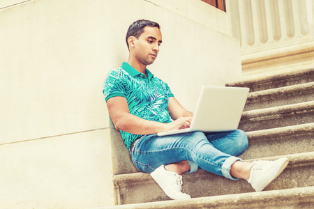 Young Hispanic American college student studying in New York, wearing green patterned Polo shirt, blue jeans, white sneakers, sitting on stairs of office building on campus, working on laptop computer