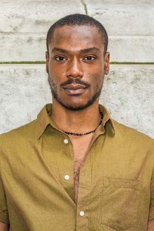 Close up, head short of Young African American Man with beard in New York, wearing green short sleeve shirt, necklace, collar unbuttoned, standing against white marble wall, seriously looking forward.