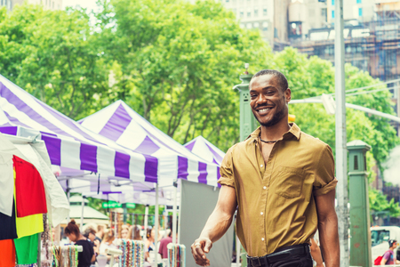 Summer Street Fair and Flea Market in New York. Young African American Man shopping, traveling in New York, wearing green short sleeve shirt, walking by street in Midtown of Manhattan, smiling. Stock fotó