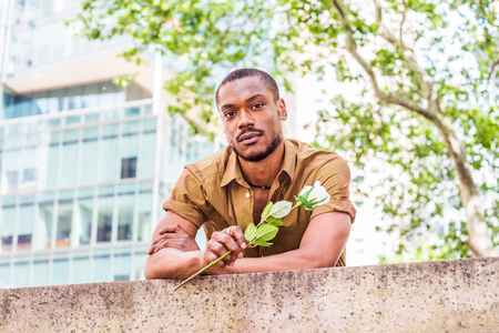 Young African American Man missing you, waiting for you in New York, wearing green short sleeve shirt, holding white rose, back bending forward on top of wall by street in Manhattan, looking forward. Stockfoto - 121632879