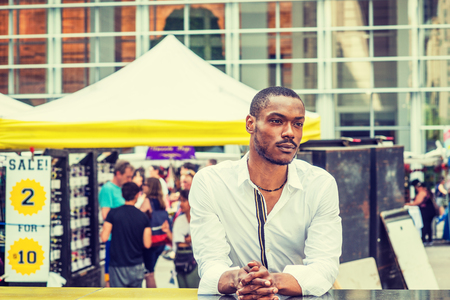 Summer Street Fair and Flea Market in New York. Young African American Man shopping, traveling in New York, wearing white shirt, standing on street in Midtown of Manhattan, thinking, lost in thought.