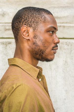 Close up, head short of Young African American Man with beard in New York, wearing green shirt,  collar unbuttoned, standing against white marble wall, seriously looking forward. Right Side View Stock fotó