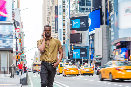 Young African American Man traveling in New York, wearing green short sleeve shirt, walking on busy street in Times Square of Manhattan, talking on cell phone. High buildings, cars on background. Banco de Imagens