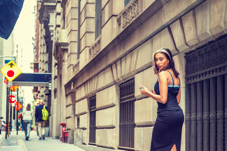 Young American Woman with black hair, dyed front top little blonde, wearing black sleeveless open back dress, walking on street by vintage wall with windows in New York, texting, turning back, looking Banco de Imagens