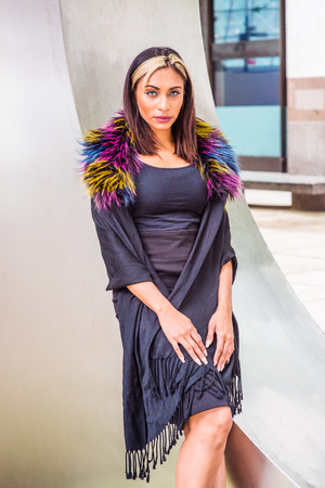 Portrait of Young American Woman in New York, with black hair, dyed front top little blonde, wearing black fit dress, wrapping shawl from shoulder down, colored faux fur scarf, standing by silver wall.