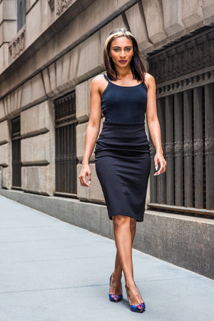 Young American Woman with black hair, dyed front top little blonde, wearing black sleeveless slim fit dress, flower patterned pumps shoes, walking on street by old style wall with windows in New York.