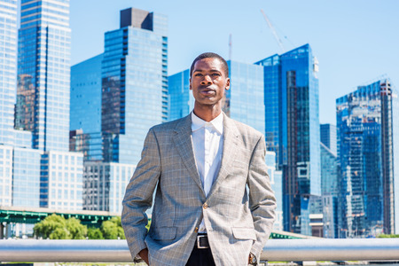 Young African American Businessman thinking outdoor in New York City, wearing patterned blazer, white shirt, standing in business district with high buildings under sun, narrowing eyes, sad, frowned.