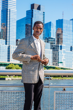 Young African American Businessman thinking outdoor in New York City, wearing patterned blazer, standing in business district with high buildings under sun, buttoning jacket, narrowing eyes, frowned.