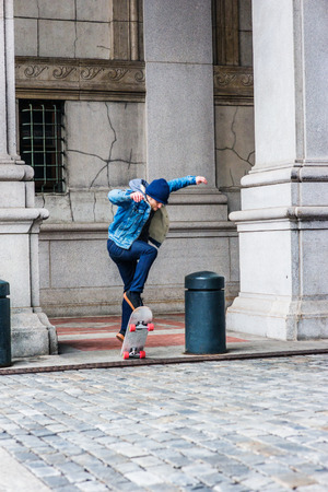Skating on street in New York City. Young college student, wearing blue Denim jacket coat, knitted hat, jeans, sneakers, standing on skateboard on vintage street on campus, jumping up, skating.