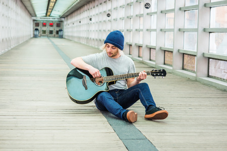 Young college student playing music, with long blonde hair, wearing knitted hat, gray T shirt, jeans, sneakers, sitting on wooden floor inside indoor walkway on campus in New York City, playing guitar Фото со стока
