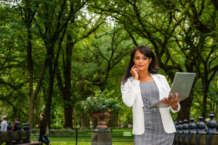 Young American Woman traveling, working in New York, wearing gray patterned open neck dress, white coat, standing at Central Park under trees, working on laptop computer, hand touching cheek, thinking