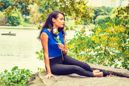 I missing you, waiting for you. Young American Woman wearing blue sleeveless shirt, black pants, shoes, holding white rose flower, sitting on rocks under green trees by lake at Central Park, New York.