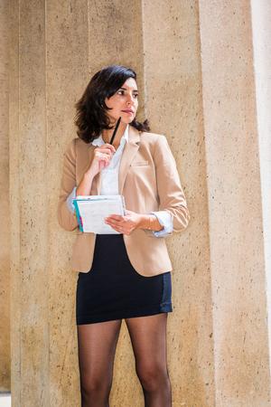 Junge amerikanische Frau, die in New York City arbeitet, trägt Cameo-Farbjacke, schwarzen kurzen Rock, Strumpfhosen, hält Kalendernotizbuch, Stift, der das Kinn berührt, gegen Säulen stehend, wegschauen, denken, Standard-Bild