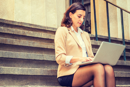 Young American Woman traveling, working in New York City, wearing beige blazer, black short skirt, tights, sitting on stairs on street outside office building, looking down, working on laptop computer