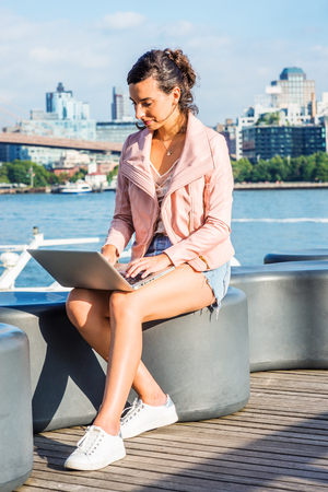 Young American Woman traveling, working in New York, wearing pink leather jacket, blue Denim shorts, white sneakers, sitting by river, working on laptop computer. Brooklyn buildings on far background