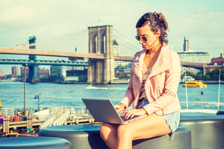 Young American Woman traveling, working in New York, wearing pink leather jacket, blue Denim shorts, sunglasses, sitting by river, working on laptop computer. Brooklyn, Manhattan bridges on background