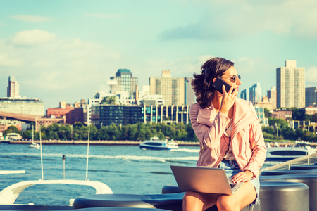 Young American Woman traveling, working in New York, wearing sunglasses, sitting by river, working on laptop computer, looking around, talking on cell phone. Brooklyn buildings, boats on background. Banco de Imagens