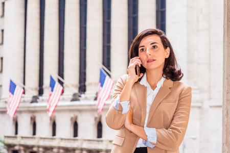 Young American Business Woman traveling, working in New York City, wearing beige blazer, standing on street outside vintage office building with American flags, looking up, talking on cell phone. Banco de Imagens