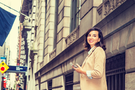 Modern Daily Life of Old City. Young American Woman traveling in New York City, wearing beige blazer, holding cell phone, walking on old style street with high buildings, turning back around, smiling.