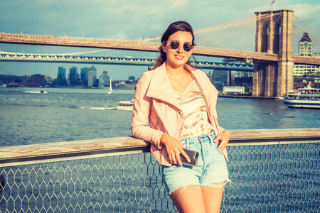Young American Woman traveling in New York, wearing pink leather jacket, blue ripped Denim shorts, sunglasses, standing by river, looking, smiling. Brooklyn, Manhattan bridges, boats on background.