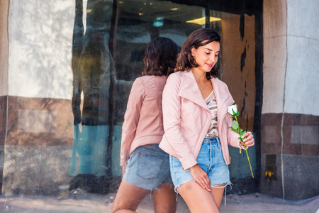 Young American Woman wearing light pink leather jacket, blue ripped Denim shorts, standing by metal mirror on street in New York, lowering head, looking at white flower held by hand, smiling, thinking Banco de Imagens