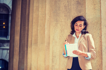 Working Anywhere. Young American Woman working in New York City, wearing Cherokee color jacket, standing against column outside office building, looking down, reading, writing on calendar notebook. Banco de Imagens