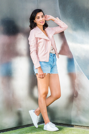 Woman Casual Fashion in New York City. Young American Lady wearing light pink leather jacket, blue ripped Denim shorts, white sneakers, standing at corner of silver metal wall with reflections.