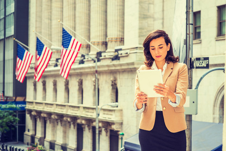 Young American Woman traveling, working in New York City, wearing Cherokee color jacket, black skirt, standing on street outside vintage office building with American flags, reading tablet computer.