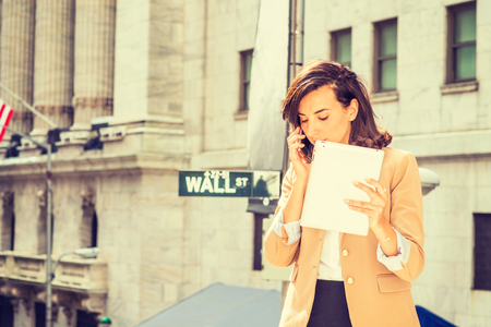 Technology in daily life. Young American Business Woman traveling, working in New York City, holding tablet computer, standing on Wall Street outside vintage office building, talking on cell phone.