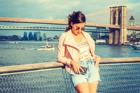 Young American Woman traveling in New York, wearing pink leather jacket, blue Denim shorts, sunglasses, standing by river, looking down, thinking. Brooklyn, Manhattan bridges, boats on background.