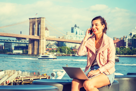 Young American Woman traveling, working in New York, sitting by East River, working on laptop computer, talking on cell phone, smiling. Manhattan bridge, Brooklyn buildings, boat on far background. Banco de Imagens